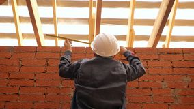 Builder measuring wooden beams in building. From below back view of man in hardhat measuring width of ceiling with wooden beams stock footage