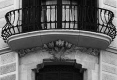 Below the balcony flowers grow. Shot in black and white, detail on the sculpture on the facade of this historic building representing some characters. Set in Royalty Free Stock Images