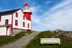 Below the Beacon. Bright Red Lighthouse with Park Bench on Sunny Day Stock Photo