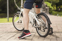 Below body of young man stopped by at public park with his bicycle. Royalty Free Stock Photography