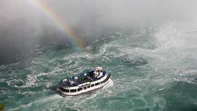 Below Niagara Falls with a tour boat and rainbow in the mist. Niagara Falls with a tour boat and rainbow in the mist of thundering water stock footage