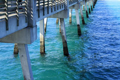 Below a Pier. The pilings and foundation structure of an Atlantic ocean cement pier or dock seen from the pier Royalty Free Stock Image