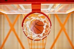 Ball falling through basketball basket stock photos
