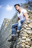 Confident attractive man on stone wall. From below shot of handsome man sitting on rack full of pebbles looking confidently away Royalty Free Stock Photo