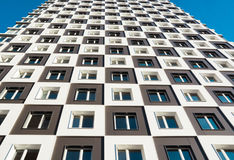 From below shot of modern and new apartment building. Photo of a tall block of flats against a blue sky. Royalty Free Stock Images
