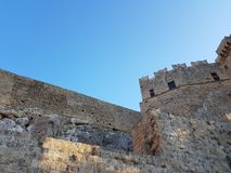 From below shot of weathered brick walls of aged castle against cloudless blue sky on amazing sunny day. From below shot of weathered brick walls of aged castle stock photo