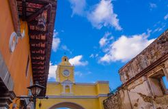 Below view of famous yellow arch with clock, lopcated in the city center of Antigua Guatemala, in a beautiful sunny day. And blue sky in Guatemala Royalty Free Stock Photo