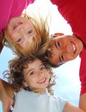 Below view of happy three children embracing. Hug each other smiling camera Royalty Free Stock Image