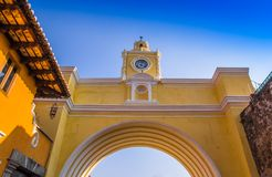 Below view of Santa Catalina arch with a gorgeous blue sky background durig a beautoful sunny day in Antigua city. In Guatemala Stock Image