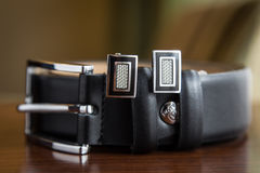 Belt. A black belt on a table and cufflinks Stock Photography