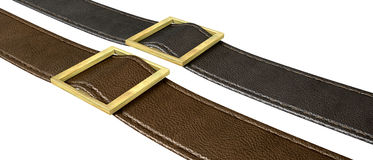 Belt And Buckle. Two side-by-side seamed leather strips in black and brown threaded through a gold belt buckle on an isolated background Stock Photo