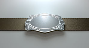 Belt Buckle And Leather. A seamed leather belt threaded through an ornate cast iron belt buckle on an isolated background Royalty Free Stock Images