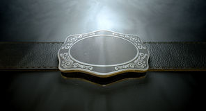 Belt Buckle And Leather. A seamed leather belt threaded through an ornate cast iron belt buckle on an isolated background Stock Images