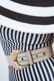 Belt with buckle. Leather belt with a buckle on a striped dress Stock Photo