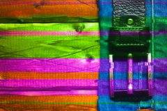 Belt with a buckle on a multi-colored woody background. Artistic photo processing. Glitch effect. Bright, colorful background stock images