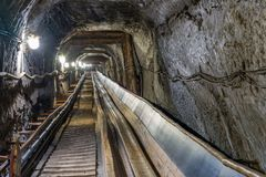 Belt conveyot in illuminated underground tunnel Royalty Free Stock Images