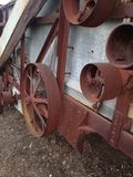 Belt Driven. Farm equipment setting in a field rusting and rotting away Royalty Free Stock Image