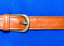 Belt leather on blue fabric Royalty Free Stock Photography