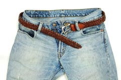 Belt over jeans open. Stylish woven leather belt over faded jeans stock photo