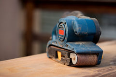 Belt sander on a wooden surface. A belt sander tool on a wooden surface with saw dust Stock Image