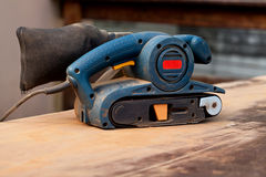 Belt sander on a wooden surface. A belt sander tool on a wooden surface with saw dust Royalty Free Stock Images