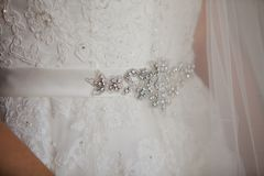 Belt with shine rhinestones on a luxurious white wedding dress Stock Photos