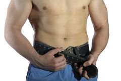 Belt for a waist. The man clasps a belt for a waist isolated on white royalty free stock images