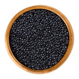 Beluga lentils in wooden bowl over white Stock Photo