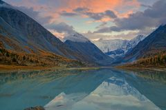 View from lake Akkem on mountain Belukha near board between Russia and Kazahstan during golden autumn. Belukha Mountain covered with snow is reflected in a royalty free stock photos