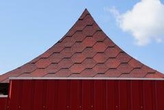 Belvédère aigu de toit des tuiles rouges derrière une barrière en métal contre le ciel image stock