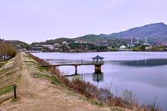 Belvédère bleu de toit sur un lac et un chemin de saleté près de lui image libre de droits