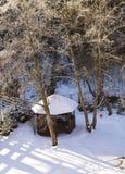 Belvédère en bois couvert dans la neige dans la lumière chaude de matin photo stock