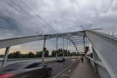 Belvarosi escondeu a ponte, com os carros e os pedestres que passam perto, no rio de tisza A ponte conecta as duas partes desta c foto de stock