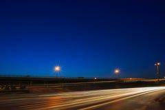 Belysning av medelkörning på asfaltvägen mot härlig bl Arkivbild