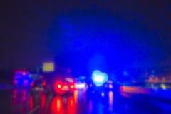 Belysning av polisbilen i natten under olycka på vägen, när regna arkivfoto