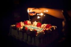 Belysning mousserar på en födelsedagkaka medan i mörkret arkivfoton