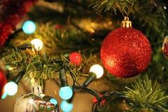 Belysninggirlander och julleksaker på julträdet arkivbild