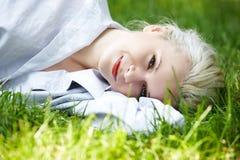 Bem estar. A mulher de sorriso feliz tem o descanso na grama Foto de Stock