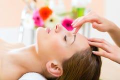 Bem-estar - mulher que obtém a massagem principal nos termas