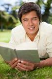 Bemanna att se framåt stundläsning en boka, som han ligger på gräs Royaltyfri Fotografi