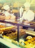 Bemanna erbjudande nya bagetter och bullar i bageri Arkivfoton
