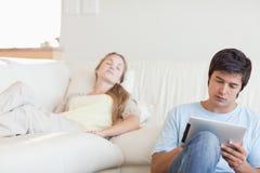 Bemanna genom att använda en tabletdatorstund som hans flickvän sovar Arkivfoton