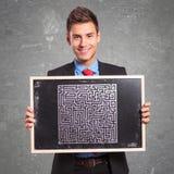 Bemanna innehav en blackboard med en utdragen maze Royaltyfria Bilder