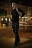Man i svart på gatan på natten Arkivfoton