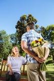 Bemannen Sie überraschend seine Freundin mit einem Blumenstrauß im Park Stockbilder