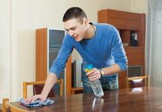 Bemannen Sie Abstaubenholztisch mit Lappen und Reiniger zu Hause stockfoto
