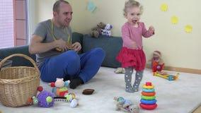 Bemannen Sie aktives Tanzen des Spielspielzeuggitarren- und -kleinkindmädchens stock footage