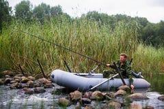 Bemannen Sie Angelrute auf dem Fluss auf einem Gummiboot liebhaberei stockfotos