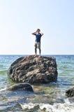 Bemannen Sie angeschwemmt auf einem Felsen im Ozean stockbild