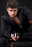 Bemannen Sie anwesendes Glas des Kognaks auf dunklem Hintergrund Stockfoto